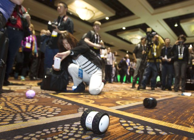 "A woman takes a photo of a Sphero 2.0 by Orbotix during ""CES Unveiled"", a media preview event to the annual Consumer Electronics Show (CES), in Las Vegas, Nevada, January 5, 2014. The Sphero 2.0 and 2B (foreground) are controlled with a smartphone. The Sphero 2.0 is already available. The 2B expected to ship in the fall of 2014, a representative said. (Photo by Steve Marcus/Reuters)"