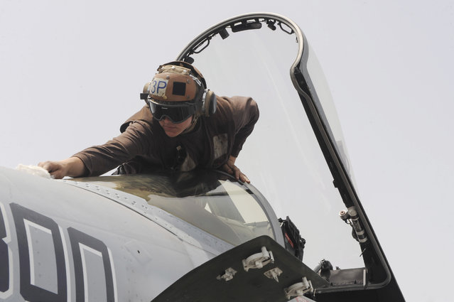 In this Thursday, April 16, 2015 image released by U.S. Navy Media Content Services, a sailor cleans the canopy of an F/A-18E Super Hornet assigned to the Knighthawks of Strike Fighter Attack Squadron 136  on the flight deck of the Nimitz-class aircraft carrier USS Theodore Roosevelt in the Fifth Fleet area of operations. (Photo by Mass Communication Specialist 3rd Class Taylor L. Jackson/U.S. Navy Media Content Services via AP Photo)
