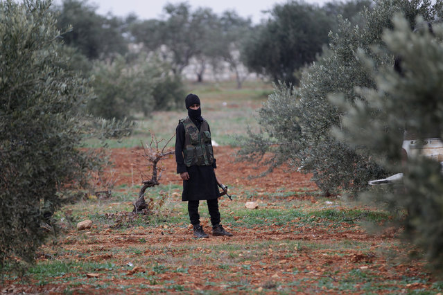 A member of al Qaeda's Nusra Front carries his weapon as he stands in an olive tree field in the southern countryside of Idlib. (Photo by Khalil Ashawi/Reuters)
