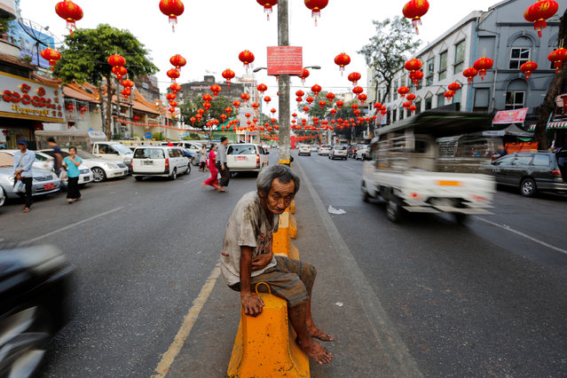 A man sits under lanterns and decorations on a street ahead of the Chinese Lunar New Year in Chinatown Yangon, Myanmar January 23, 2017. (Photo by Soe Zeya Tun/Reuters)