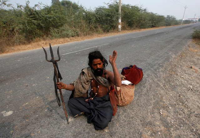 A snake charmer sits on a road with his belongings after returning home from a month-long trip in Jogi Dera (snake charmers settlement), in the village of Baghpur, in the central state of Uttar Pradesh, India January 16, 2017. (Photo by Adnan Abidi/Reuters)