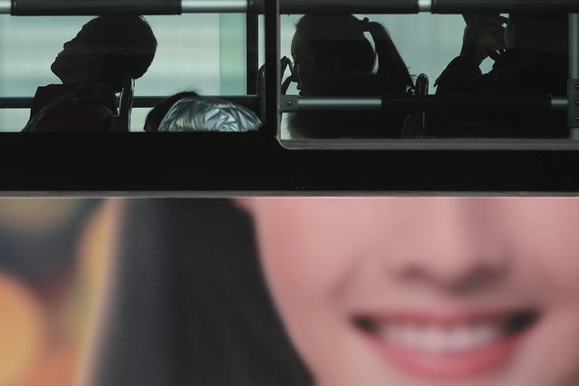 In this January 12, 2019, photo, commuters ride on a bus with a smiling face advertisement at the Central Business District in Beijing. China's slowing economy is squeezing the urban workers and entrepreneurs the ruling Communist Party is counting on to help transform this country from a low-wage factory floor into a prosperous consumer market. (Photo by Andy Wong/AP Photo)