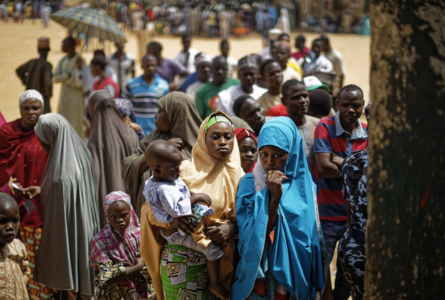 Women queue in the midday sun to cast their votes at a polling station in Kano, northern Nigeria Saturday, February 23, 2019. Nigerians are going to the polls for a presidential election Saturday, one week after a surprise delay for Africa's largest democracy. (Photo by Ben Curtis/AP Photo)