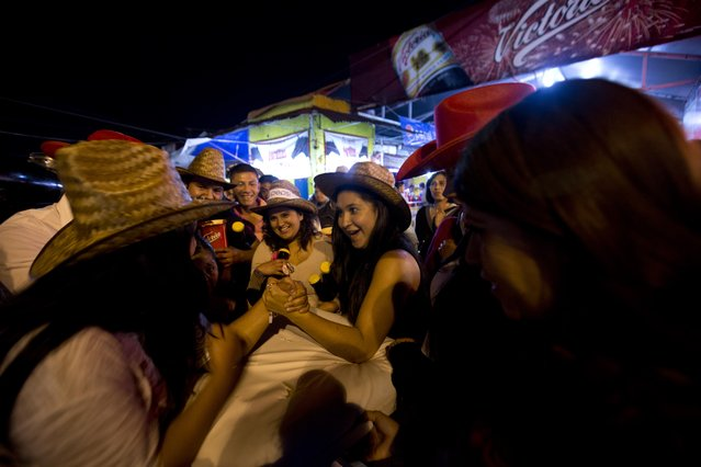 In this April 10, 2015 photo, women play an arm wrestling game at the Texcoco Fair on the outskirts of Mexico City. A beer vendor set up the game outside his booth, and gave winners red cowboy hats and drinking glasses. (Photo by Eduardo Verdugo/AP Photo)