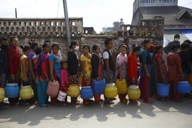People stand in a queue to fill water near the makeshift shelters after Saturday's earthquake in Kathmandu, Nepal April 28, 2015. (Photo by Navesh Chitrakar/Reuters)