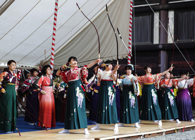 """Participants shoot arrows wearing """"Furisode"""", a long sleeved kimono, take part in an archery event for 20-year-olds to celebrate their coming-of-age at Sanjusangendo Temple on January 17, 2016 in Kyoto, Japan. Some 2,000 people took part in the annual event. (Photo by Taro Karibe/Getty Images)"""