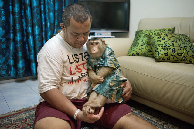 "This photo taken on April 22, 2015, shows Jamil Ismail (Jamilkucing) hugging his female pet monkey named ""Shaki"", dressed in a Malaysian cultural outfit called Baju Kurung, at Jamil's house in Kuala Lumpur. (Photo by Mohd Rasfan/AFP Photo)"