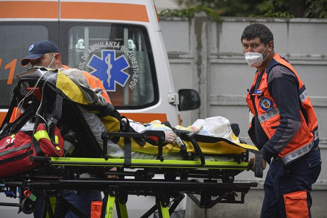 Paramedics bring an elderly patient to the emergency room, turned into a CODIV-19 unit due the high number of cases, at the Bagdasar-Arseni hospital in Bucharest, Romania, Tuesday, October 12, 2021. Romania reported on Tuesday nearly 17,000 new COVID-19 infections and 442 deaths, the highest number of coronavirus infections and deaths in a day since the pandemic started, as the nation's health care systemstruggles to cope with an acute surge of new cases. (Photo by Andreea Alexandru/AP Photo)