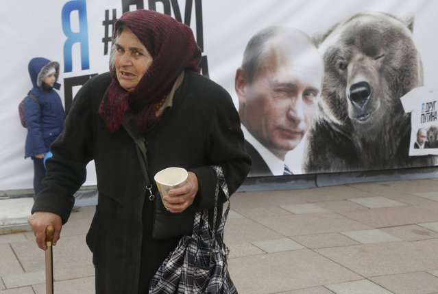 "A woman walks as she begs  near a poster depicting Russian President Vladimir Putin in St.Petersburg, Russia, Friday, May 1, 2015. The slogan reads ""I am a Putin's friend"". (Photo by Dmitry Lovetsky/AP Photo)"