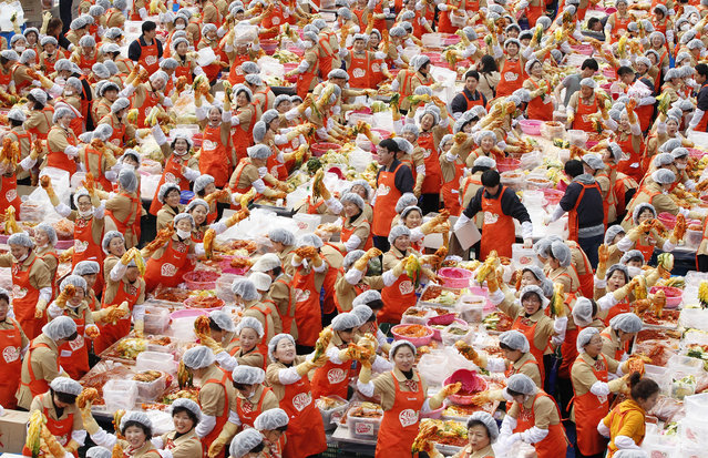 Women pose for the cameras as they make the traditional Korean side dish kimchi, or fermented cabbage, at a charity event at the Seoul City Hall Plaza November 8, 2011. About 2,000 volunteers made 270 tonnes of kimchi to give away to needy people during the winter season. (Photo by Jo Yong-Hak/Reuters)