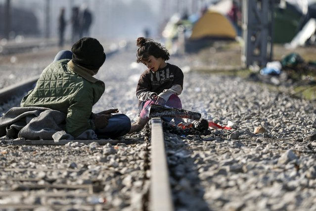 A girl sits on railway tracks at a makeshift camp for refugees and migrants at the Greek-Macedonian border near the village of Idomeni, Greece, March 19, 2016. (Photo by Alkis Konstantinidis/Reuters)