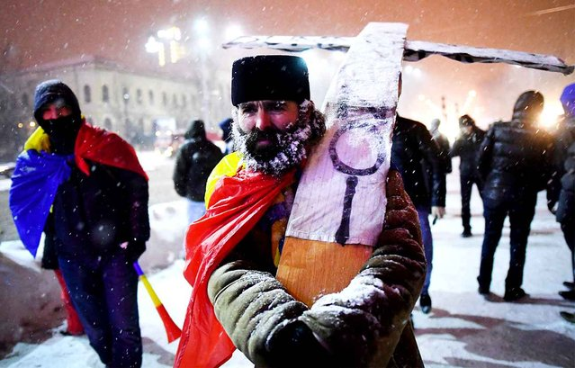 A priest wearing the Romanian flag carries a makeshift cross in front of the government headquarters in Bucharest, during a protest against controversial corruption decrees on February 8, 2017. Around 2,000 people protested in Bucharest for the ninth day in row asking for the resignation of PSD (Social Democratic Party) rulled government. (Photo by Daniel Mihailescu/AFP Photo)