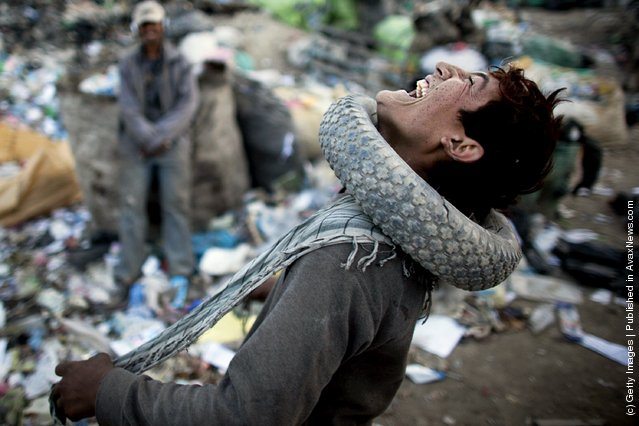 An Afghan man wears a tire around his neck while sorting through plastic and metal items near a rubbish dump