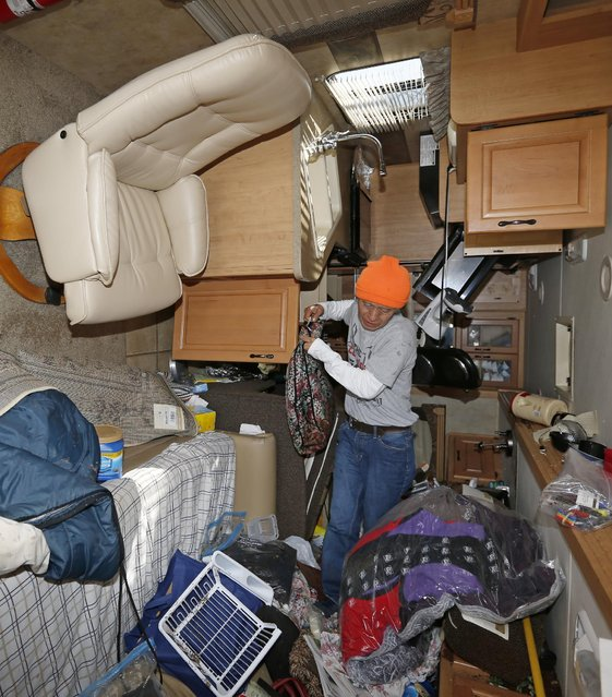Yuki Fukui makes his way through his recreational vehicle, which is laying on it's side due to the Wednesday severe storms, with salvaged items, in Oklahoma City, Thursday, May 7, 2015. Gov. Mary Fallin has declared a state of emergency in 12 Oklahoma counties hit by tornadoes, severe storms, straight-line winds and flooding. (Photo by Sue Ogrocki/AP Photo)