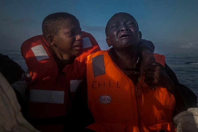 A handout image provided by the World Press Photo (WPP) organization on 13 February 2017 shows a picture by Santi Palacios that won the General News – Second Prize, Singles award of the 60th annual World Press Photo Contest, it was announced by the WPP Foundation in Amsterdam, The Netherlands on 13 February 2017. Caption: An 11-year-old girl from Nigeria (left), who said her mother died in Libya, cries next to her 10-year-old brother aboard an NGO rescue boat, on 28 July 2016. The children had sailed for hours in an overcrowded rubber boat with other refugees during a rescue operation on the Mediterranean Sea, about 23 kilometers north of Sabratha, Libya. Libyan smugglers often take advantage of refugees, charging anywhere from $750 to $3500 for a place on typically dangerous boats they say are heading to Italy. (Photo by Santi Palacios/EPA/World Press Photo)