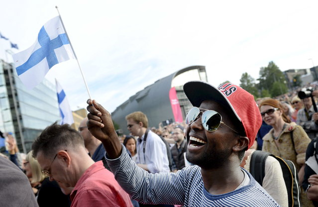 5. FINLAND: Mire Ibrahim waves the Finnish flag during a demonstration against racism where an estimated 15,000 people attended in Helsinki, Finland July 28, 2015. (Photo by Vesa Moilanen/Reuters/Lehtikuva)