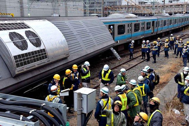 Japan Railway workers inspect a damaged train near Kawasaki station in Kawasaki, suburban Tokyo on February 23, 2014. An out of service train clashed with an un-man maintenance car and two train crews were injured. (Photo by Yoshikazu Tsuno/AFP Photo)