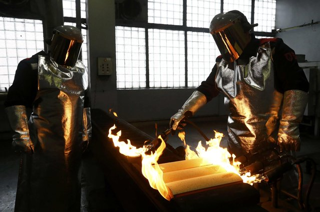 Employees cast gold ingots at the Prioksky Non-Ferrous Metals Plant in Kasimov, Russia February 14, 2017. (Photo by Sergei Karpukhin/Reuters)
