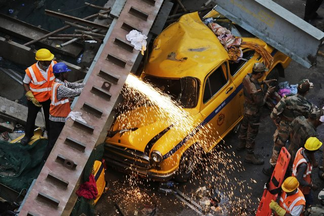 Rescue workers cut through parts of a partially collapsed overpass in Kolkata, India,Thursday, March 31, 2016. (Photo by Bikas Das/AP Photo)