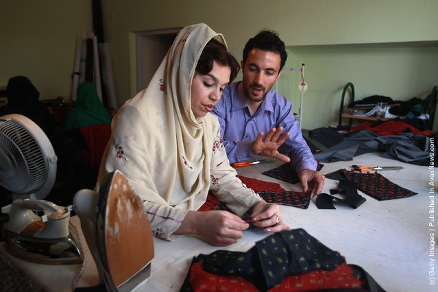 Afghan master tailor Ahmed Jamshid Naser instructs Habiba Uthri in making finished garments at the Afghan Women Business Council