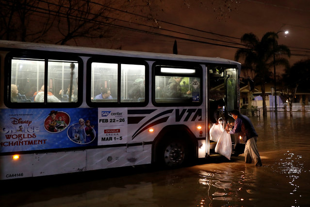 A man places bags on an awaiting evacuation bus after heavy rains overflowed nearby Coyote Creek in San Jose, California, U.S. February 21, 2017. (Photo by Stephen Lam/Reuters)