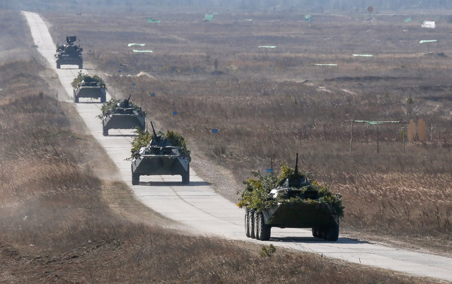Ukrainian military vehicles drive on a road during a military drill at the military shooting range called Goncharivka, 120 kilometers north-east from Kiev, Ukraine, 14 March 2014. Tanks, helicopters, artillery and paratroopers took part at a complex military exercise, inspected by the Ukraine's acting President Olekasndr Turchynov (not pictured), two days before the Crimean referendum. (Photo by Sergey Dolzhenko/EPA)