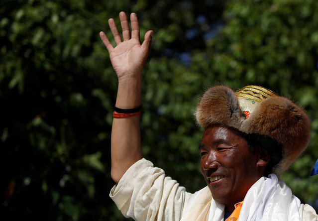Kami Rita Sherpa, 49, a Nepali mountaineer, waves towards media personnel upon his arrival after climbing Mount Everest for the 24th time, creating a new record for the most summits of the world's highest mountain, in Kathmandu, Nepal on May 25, 2019. (Photo by Navesh Chitrakar/Reuters)