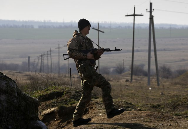 A Ukrainian soldier stands guard outside a Ukrainian Army military camp set up on a field close to the Russian border in east Ukraine March 24, 2014. (Photo by Yannis Behrakis/Reuters)