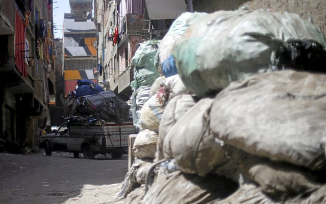 """A vehicle carries garbage near a small recycling factory in front of a mural painted on the walls of houses in Zaraeeb, created by French-Tunisian artist El Seed, in the shanty area known also as Zabaleen or """"Garbage City"""" on the Mokattam Hills in eastern Cairo, Egypt, April 4, 2016. (Photo by Amr Abdallah Dalsh/Reuters)"""
