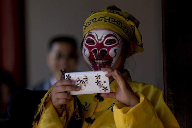 A Peking opera performer uses her mobile photo to take photos after she performed for visiting U.S. first lady Michelle Obama at the Summer Palace in Beijing, Saturday, March 22, 2014. (Photo by Alexander F. Yuan/AP Photo)