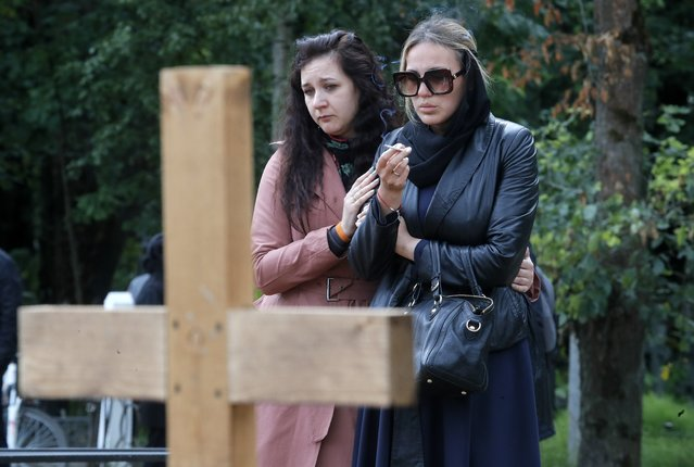 Two women mourn at the grave of one of the 14 crew members who died in a fire on a Russian navy's deep-sea research submersible, at the Serafimovskoye memorial cemetery during a funeral ceremony in St. Petersburg, Russia, Saturday, July 6, 2019. (Photo by Dmitri Lovetsky/AP Photo)