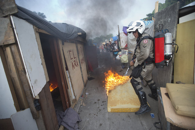 A firefighter enters an area occupied by squatters during an eviction in Rio de Janeiro, Brazil, Thursday, April 10, 2014. Squatters in Rio de Janeiro are clashing with police after a Brazilian court ordered that 5,000 people be evicted from abandoned buildings of a telecommunications company. Officers have used tear gas and stun grenades to try to disperse the families. (Photo by Silvia Izquierdo/AP Photo)