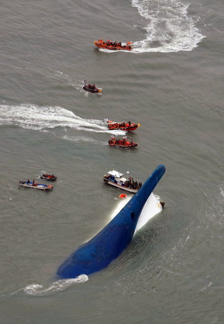 In this photo released by Jeollanamdo via Yonhap News Agency, South Korean rescue team boats and fishing boats try to rescue passengers of a ferry sinking off South Korea's southern coast, in the water off the southern coast near Jindo, south of Seoul, Wednesday, April 16, 2014. (Photo by AP Photo/Jeollanamdo via Yonhap)