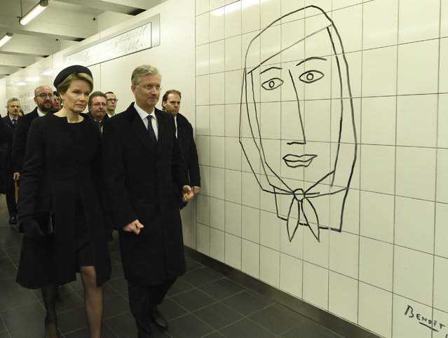 Queen Mathilde of Belgium (L) and King Philippe of Belgium (R) pass by a Benoit Van Innis artwork as they arrive for a minute of silence at 09:11 in the Maelbeek - Maalbeek subway station as tribute to the victims of last year terrorist attacks in Brussels, on March 22, 2017. Belgium marks the first anniversary of the Islamic State bombings in Brussels, one at the airport and the other in the metro, in which 32 people were killed and more than 320 wounded with ceremonies showing that the heart of Europe stands defiant. (Photo by Didier Lebrun/AFP Photo)