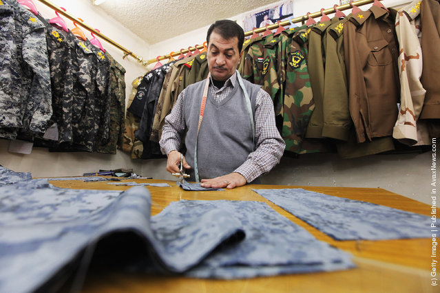 A tailor cuts cloth while making a police unform in a shop that sells uniforms to members of Iraq's military and police forces