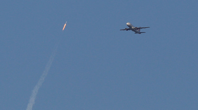 A recycled SpaceX Falcon 9 rocket soars toward space above a Virgin Airlines passenger jet, which had just departed Orlando International Airport, in Orlando, Florida, March 30, 2017. The launch marked the first time ever that a rocket was reused for spaceflight. (Photo by Gregg Newton/Reuters)