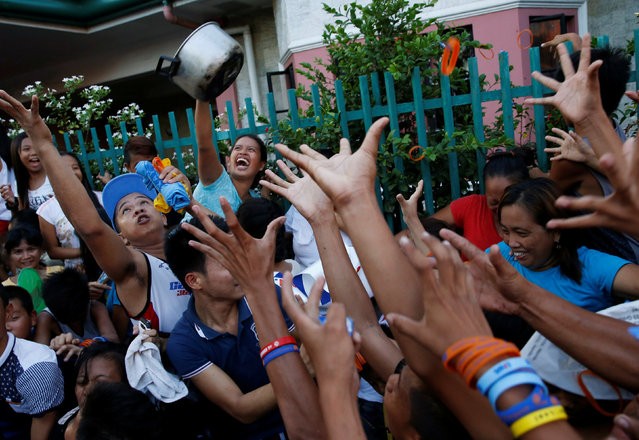 Supporters of Filipino boxer and Senatorial candidate Manny Pacquiao, jostle for souvenirs thrown by Pacquiao during election campaigning in Malabon Metro Manila in the Philippines May 6, 2016. (Photo by Erik De Castro/Reuters)