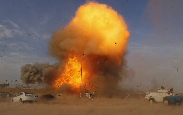 An explosion is seen during a car bomb attack at a Shi'ite political organisation's rally in Baghdad, April 25, 2014. A series of explosions killed 18 people at a Shi'ite political organisation's rally in Iraq on Friday, police and medical sources said. (Photo by Thaier al-Sudani/Reuters)