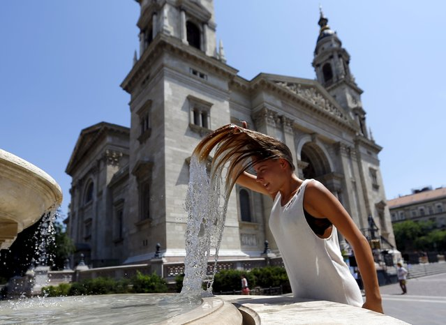 A woman dips her head into a fountain in Budapest, Hungary July 6, 2015. Over the weekend, a heat wave has reached Hungary with temperatures topping 38 degrees Celsius (100.4 degrees Fahrenheit). (Photo by Laszlo Balogh/Reuters)