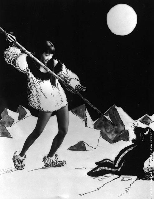 1928: American-Chinese actress Anna May Wong aiming a spear at a cartoon sea lion