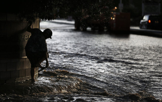 A man adjusts his sandals while wading through floodwater Monday, July 6, 2015, in Las Vegas. Heavy rain throughout the area prompted the National Weather Service to issue a flash flood warning for parts of Las Vegas. (Photo by John Locher/AP Photo)