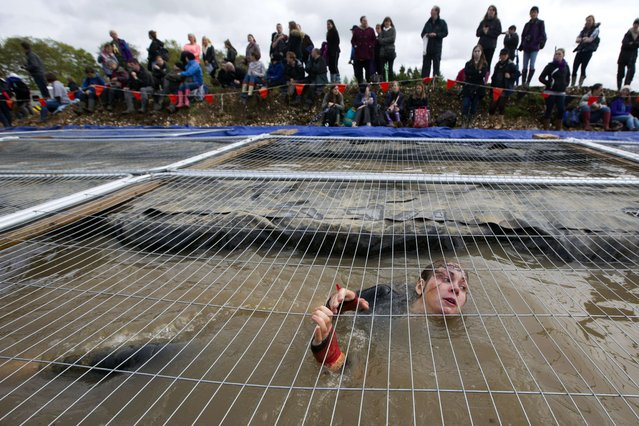 A participant swims backwards through water underneath a mesh wire fence during the Tough Mudder endurance race in Henley on Thames, West of London, on April 26, 2014. The course is set out over 10-12 miles (18-20 km) with 20 obstacles. (Photo by Justin Tallis/AFP Photo)