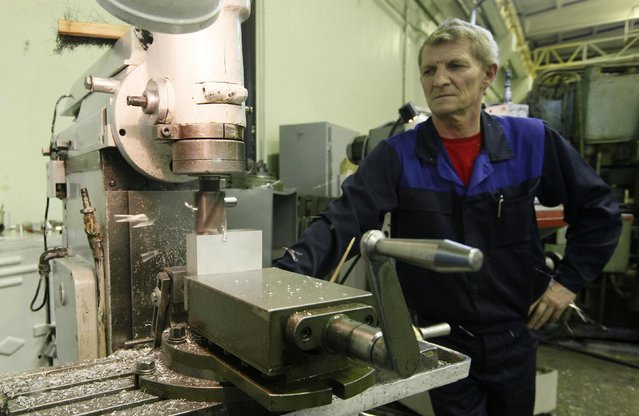 A milling-machine operator produces aluminium details for space satellites at a workshop of the Reshetnev Information Satellite Systems company in the Siberian town of Zheleznogorsk April 1, 2014. (Photo by Ilya Naymushin/Reuters)