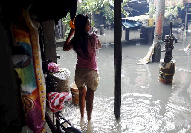 A teenager takes a bath in a flooded squatter colony beside a creek in Meycauayan Bulacan north of Manila in the Philippines July 10, 2015. (Photo by Erik De Castro/Reuters)