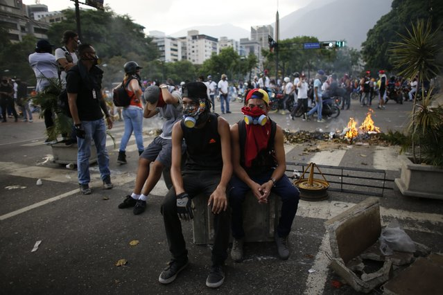 Anti-government protesters rest during a break in clashes with security forces in Caracas, Venezuela, Wednesday, April 19, 2017. (Photo by Ariana Cubillos/AP Photo)
