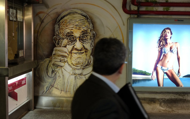 A man looks at an official painting by French street artist Christian Guemy, aka C215, representing Pope Francis on May 9, 2014 at the Piazza di Spagna metro station in Rome. Pope's portrait is part of an artistic project launched by Rome's transportation company Atac. (Photo by Alberto Pizzoli/AFP Photo)