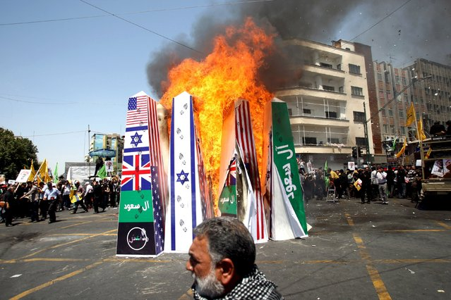 "Iranian demonstrators burn symbolic structures depicting the flags of the U.S., Britain, and Israel during a rally marking al-Quds (Jerusalem) Day in Tehran July 10, 2015. The green banner reads, ""Saud family"", referring to the royal family of Saudi Arabia. (Photo by Reuters/Stringer/TIMA)"