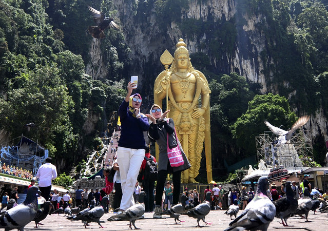 ourists take selfie with the Lord Murugan statue at Batu Caves in Kuala Lumpur, Malaysia on Friday, April 21, 2017. (Photo by Daniel Chan/AP Photo)