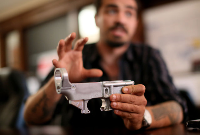 Karras displays a lower receiver for an AR-15 assault rifle at Ares Armor in Oceanside, Calif. Karras, a former Marine who was stationed at nearby Camp Pendleton, opened his store after serving in Iraq and Afghanistan. He sells combat packs, slings, tactical belts and carriers for wearing armor. (Photo by Sandy Huffaker for The Washington Post)