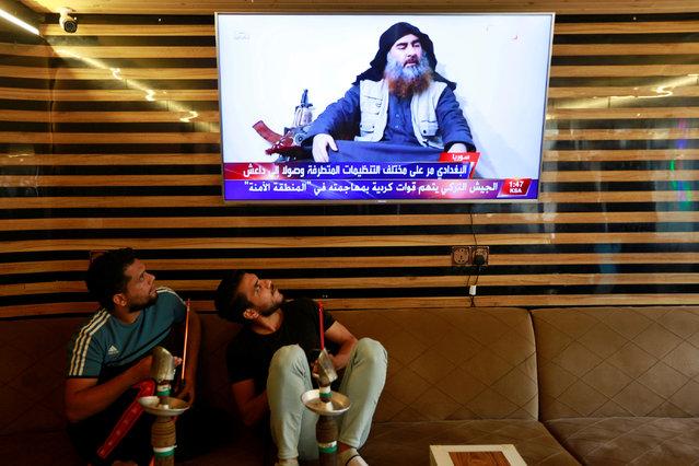 Iraqi youth watch the news of Islamic State leader Abu Bakr al-Baghdadi death, in Najaf, Iraq on October 27, 2019. (Photo by Alaa al-Marjani/Reuters)